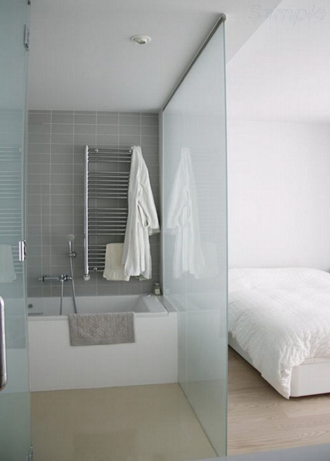 Glass partition separates the sitting area and the bathroom