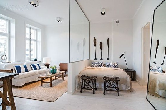 Glass partitions separate the sleeping space from other areas of the studio apartment
