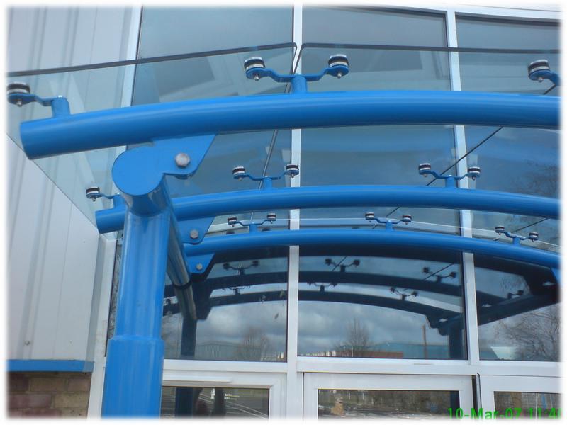 Стеклянный навес на металлических трубах с точечными креплениями стеклянных панелей